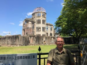 SR Staley standing before the iconic image of the atomic bomb's aftermath: the A-Bomb Dome.